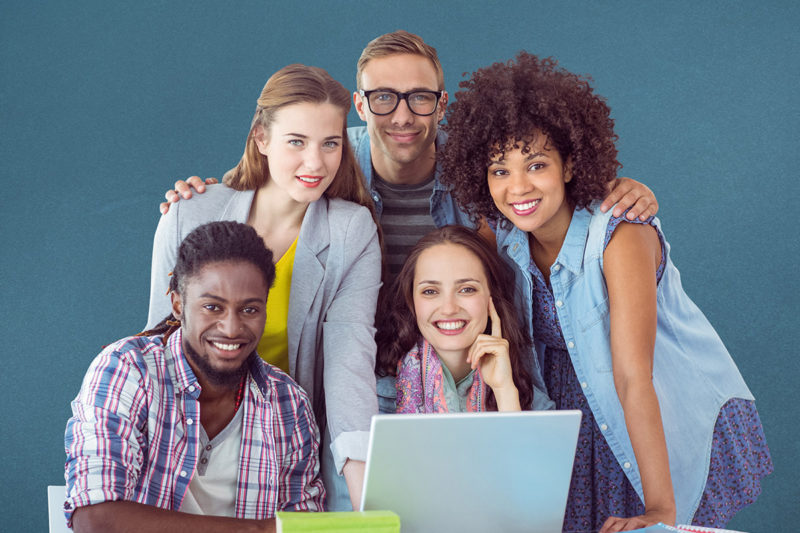grupa osób pozująca do zdjęcia przy laptopie