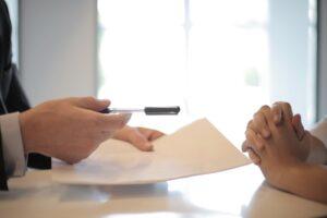 Długopis z kartką papieru w rękach jednej osoby